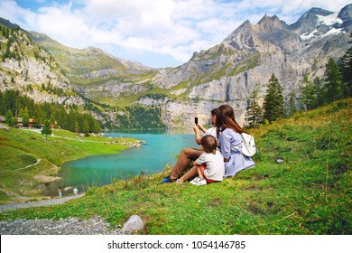 young happy family of tourists photographing the nature of the beautiful blue natural lake oeschinensee, in Switzerland, a fantastic mountain landscape overlooking the water and forest,