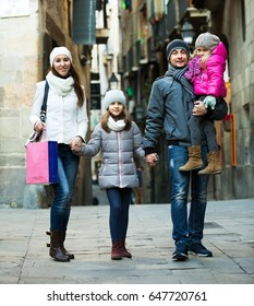 Young happy family with two children posing outdoors in winter. Focus on woman