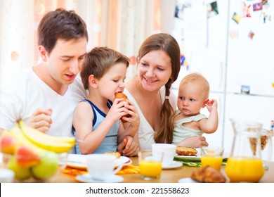 Young happy family with two kids having breakfast together at home