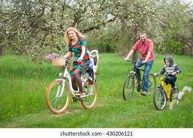 Young happy family with two kids riding bicycles in spring garden, little baby in bicycle chair, in the basket lay a bouquet of lilacs
