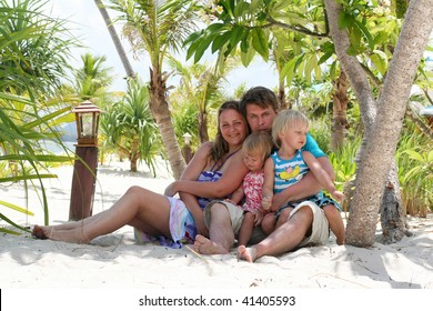 Young happy family under the palm on tropical sand beach