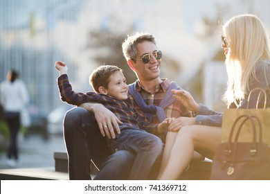 Young happy family walking down the street after shopping