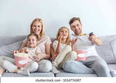 young happy family watching movie on couch at home