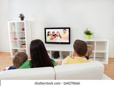 Young happy family watching TV at home