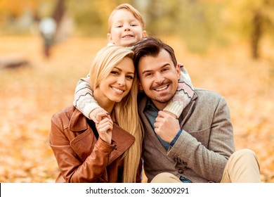 Young happy family while walking in the autumn park.