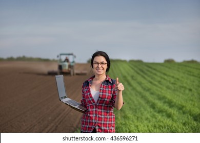 Young happy farmer girl standing on field with laptop and showing ok sign with thumb up. Tractor in background