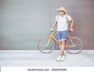 Young Happy Fashion Hipster Man with Cool Yellow Vintage Bicycle. Male Leaning at his Bike while Standing against Grey Background. Outdoors Portrait of Handsome Guy in Summer Clothes.