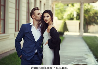 Young Happy fashionable couple in the city in stylish clothes.The man Wearing in business suit, the woman in romantic sexy dress with lace and coat