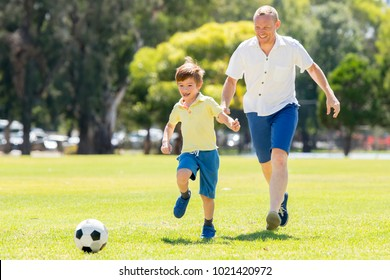 young happy father and excited 7 or 8 years old son playing together soccer football on city park garden running on grass kicking the ball in dad and boy relationship and healthy sport lifestyle