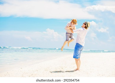 Young happy father playing with his little son standing barefoot at the beach with ocean and beautiful clouds on background. Having fun with the kid in summer coast on holidays
