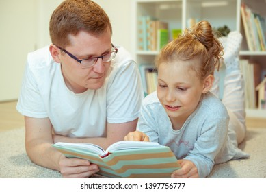 Young happy father reading book with  cute daughter at home lying on the floor