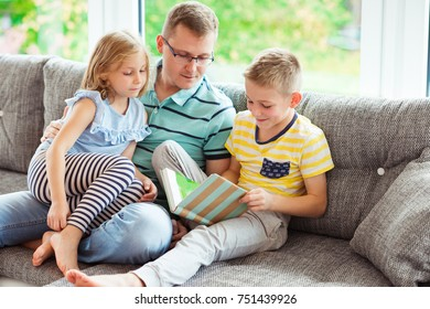 Young happy father reading book with two cute children at home