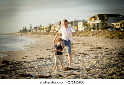 young happy father and son playing on the beach with barefoot in sand and water, the little kid smiling and having fun together with dad in Summer vacation concept