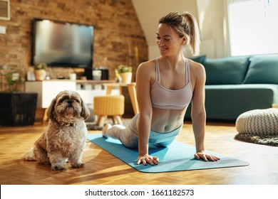 Young happy female athlete practicing Yoga while dog is sitting next to her at home.