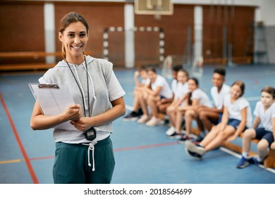 Young happy female coach looking at camera while having PE class with elementary students at school gym.  - Shutterstock ID 2018564699