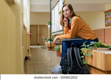Young happy female college student sitting in the hallway at her school. Education concept.