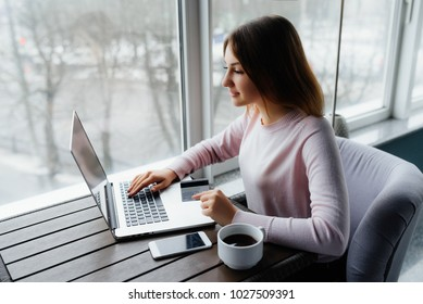 Young happy female holding credit card and using laptop computer. Online shopping concept. Payment Transaction at Computer using Credit Card