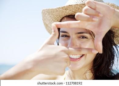 junges glückliches Weibchen, das durch einen Rahmen aus ihren Fingern schaut