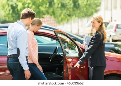 Young Happy Female Opening New Red Car Door For Customer