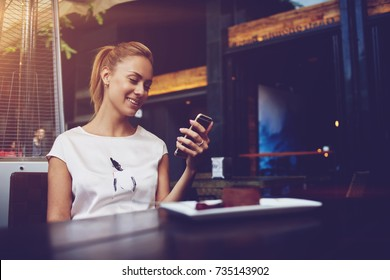 Young happy female reading good news on her mobile phone while sitting in modern coffee shop interior, gorgeous hipster girl with beautiful smile watching funny video on cell telephone during lunch