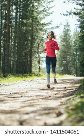 Young happy female runner listening to music while jogging along a sunny trail in forest.