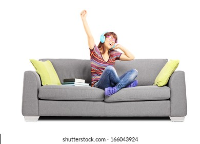 Young happy female student listening music seated on a sofa isolated on white background