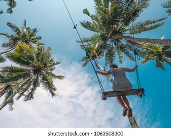 Young happy female swinging on a tropical jungle swing under palm trees. Summer relaxing vacation in paradise in Bali island, Indonesia. Blue sky on the background. Summer holidays and travel icon.