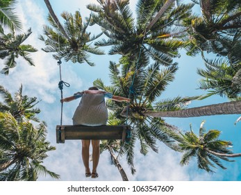 Young happy female swinging on a tropical jungle swing under palm trees. Summer relaxing vacation in paradise in Bali island, Indonesia. Blue sky on the background. Summer holidays and travel concept.