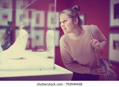 Young happy   female visitor looking at exhibition in museum of ancient sculpture