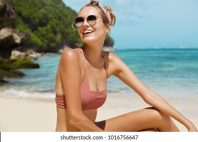 Young happy female wears sunglasses, headband and swimsuit, poses against sea cliff and beautiful blue water, has vacations on exotic beach, poses for travel magazine. Summer and leisure concept
