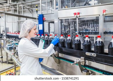 Young happy female worker in bottling factory checking juice bottles before shipment. Inspection quality control.