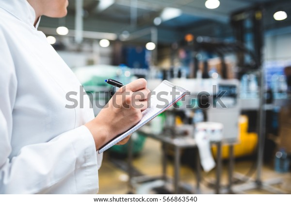 Young happy female worker in factory writing notes about water bottles or gallons before shipment. Inspection quality control. Selective focus on hand.