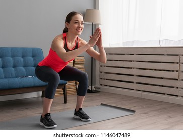 Young happy fitness woman doing squat exercise at home