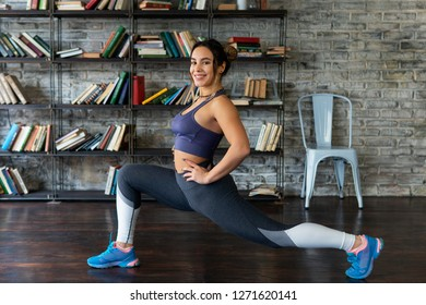 Young happy fitness woman doing leg stretching and smiling at home