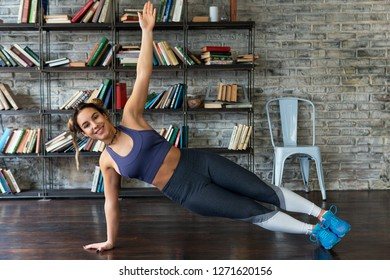 Young happy fitness woman doing side plank exercise during yoga on floor at home