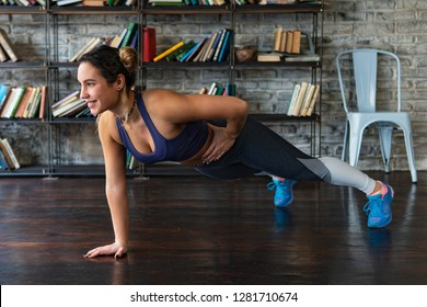 Young happy fitness woman doing push ups workout on one arm on floor at home