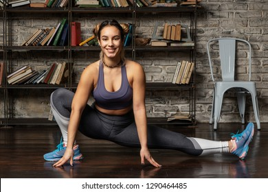 Young happy fitness woman doing leg stretching exercise at home