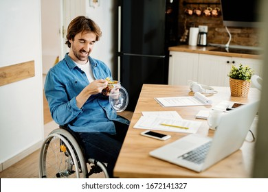 Young happy freelancer worker in wheelchair having lunch break while working at home.