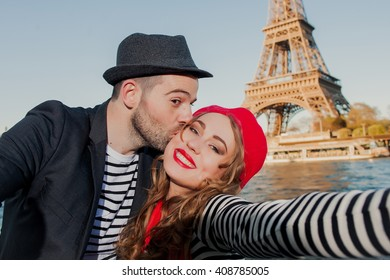 Young happy french couple taking selfie under the Eiffel Tower in Paris, France