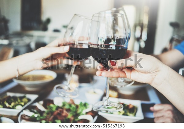 Young happy friends cheering with glasses of red wine, family dinning at home, enjoyment and party concept, homemade cuisine and healthy food concept