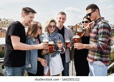 Young happy friends drinking beer before festival at outdoors pub on roof, toasting and laughing, copy space. Friendship and celebration concept