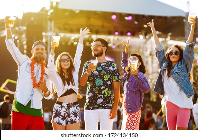 Young happy friends drinking beer and having fun at music festival together. Beach party, summer holiday, vacation concept. Friendship and celebration concept.