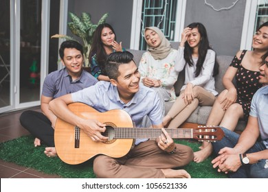 Young happy friends having party, one playing guitar and the other singing together