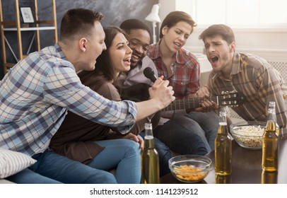 Young happy friends having party, playing the guitar and singing at home