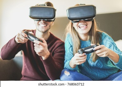 Young happy friends playing video games wearing virtual reality glasses in their apartament - Cheerful people having fun with new trends technology - Gaming concept - Focus on woman front headset