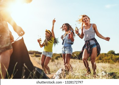 The young happy friends are preparing for camping. They're installing a tent on a suitable place in a meadow and their girlfriends are offering the beer to them. Girls dance in nature.