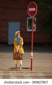 Young happy funny dressed woman  with retro suitcase stands on the street near red road sign