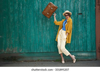 Young happy funny (vintage) dressed woman waves retro suitcase. Old green fence on the background. Picture ideal for illustating woman magazines.