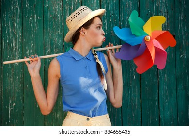 Young happy funny (vintage) dressed woman with colorful weather vane,looking like flower. Old green fence on the background. Picture ideal for illustating woman magazines.