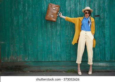 Young happy funny (vintage) dressed woman waves retro suitcase. Old green fence on the background.Picture ideal for illustating woman magazines.